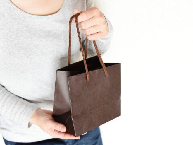 茶色い紙袋のお土産を渡す人
